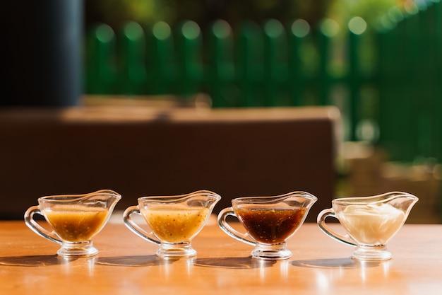 Variedade de molhos em uma tigela, mostarda, churrasco, maionese, teriyaki, na mesa de madeira