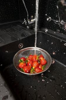 Variedade de morangos sendo lavados