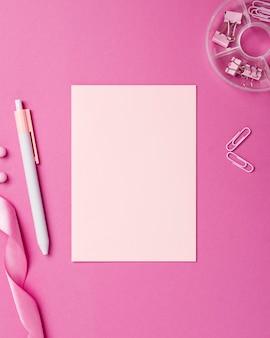 Variedade de natureza morta monocromática com objetos de papelaria rosa