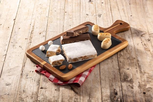 Variedade de nogado e maçapão de natal na mesa de madeira