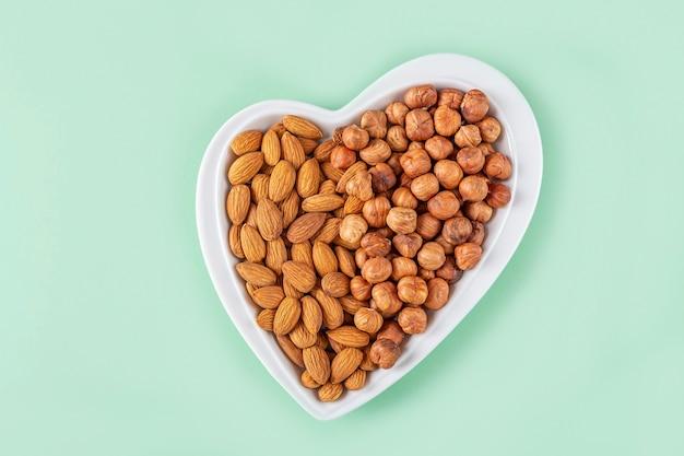 Variedade de nozes, avelãs, amêndoas em prato em forma de coração lanches vegetarianos saudáveis.