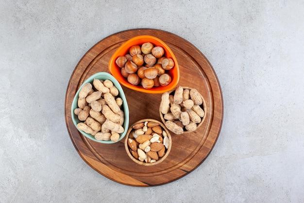 Variedade de nozes diferentes, classificadas em várias tigelas em uma bandeja de madeira com fundo de mármore. foto de alta qualidade