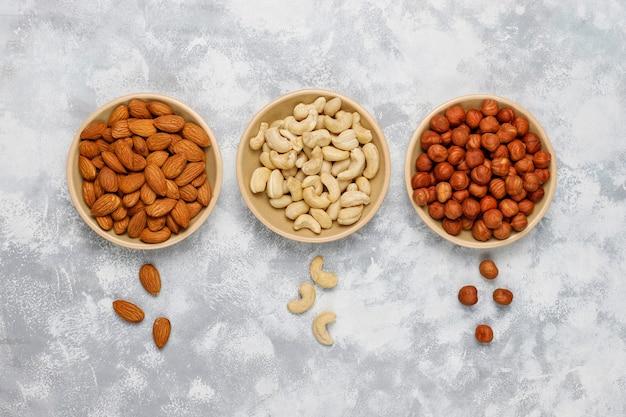 Variedade de nozes em pratos de cerâmica. caju, avelãs, nozes, pistache, nozes, pinhões, amendoim, passas. vista superior
