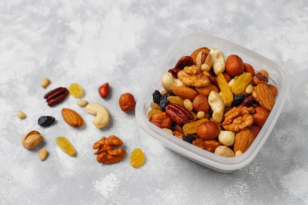 Variedade de nozes em recipiente plástico. caju, avelãs, nozes, pistache, nozes, pinhões, amendoim, passas. vista superior