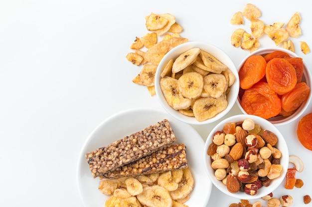 Variedade de nozes, frutas secas e barra de granola em tigelas com fundo branco vista superior