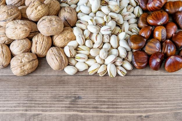 Variedade de nozes saudáveis frescas maduras nozes, pistache e castanhas no fundo de madeira