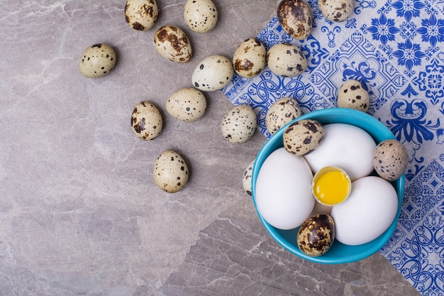 Variedade de ovos em uma xícara em superfície cinza