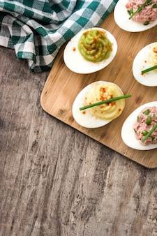 Variedade de ovos recheados com abacate e atum na vista superior de mesa de madeira. copie o espaço