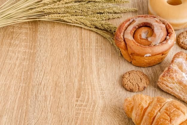 Variedade de pães frescos, bolos, croissant e trigo na superfície da mesa de madeira