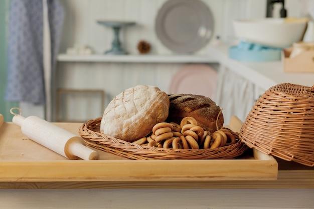 Variedade de pães perto de uma cesta de vime em uma mesa em uma cozinha rústica. composição na cozinha do estúdio fotográfico.