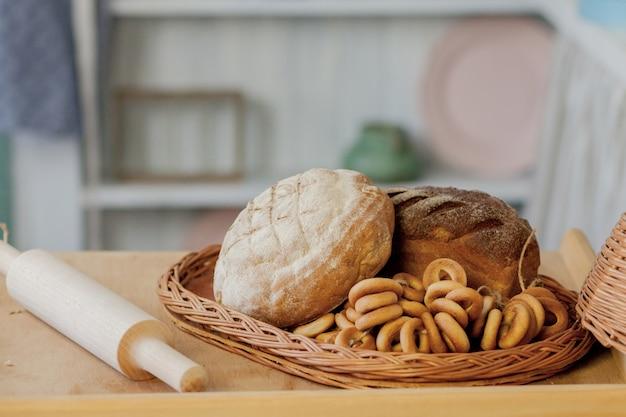 Variedade de pães perto de uma cesta de vime em uma mesa em uma cozinha rústica.