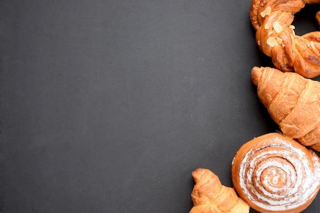 Variedade de pães recém-assados no quadro negro. fundo de padaria