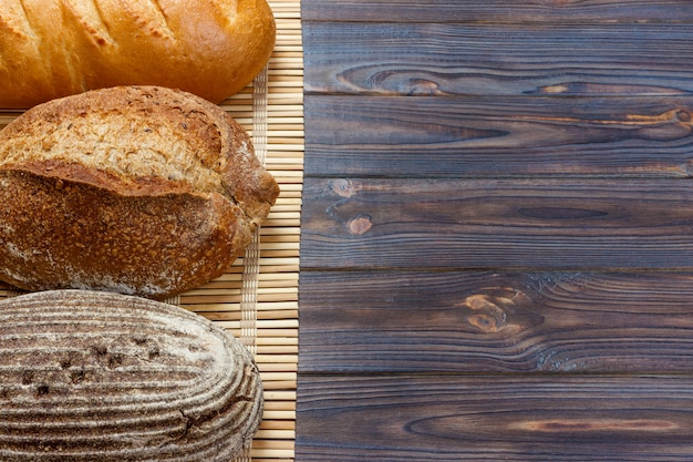 Variedade de pão assado na mesa de madeira. vista superior com espaço de cópia