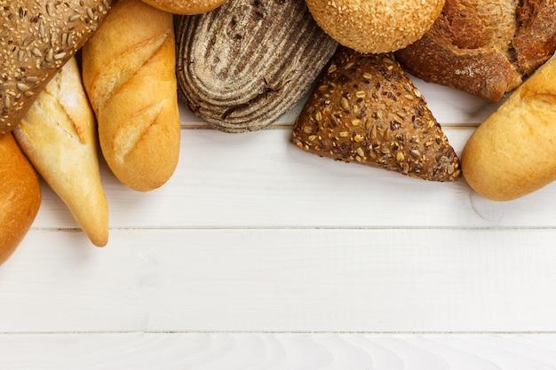 Variedade de pão assado na superfície da mesa de madeira branca.