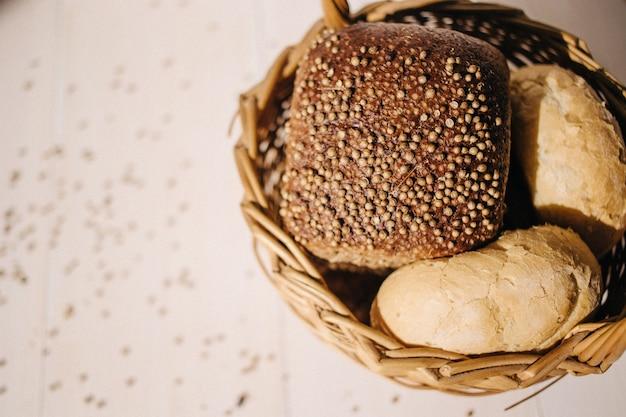 Variedade de pão assado no fundo da mesa de madeira branca, luz dura