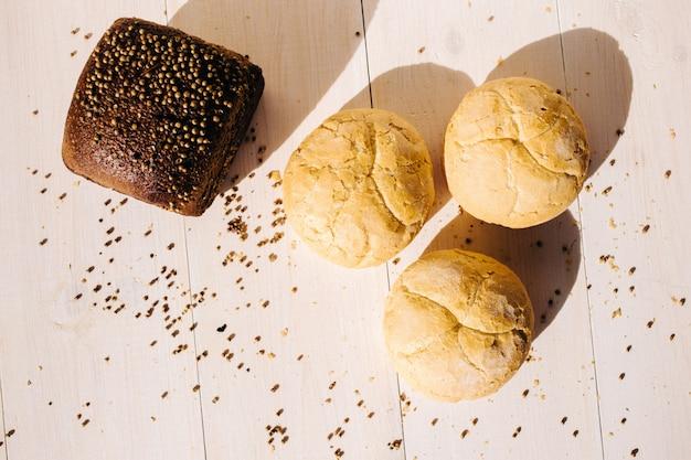 Variedade de pão assado no fundo da mesa de madeira branca, luz dura Foto Premium