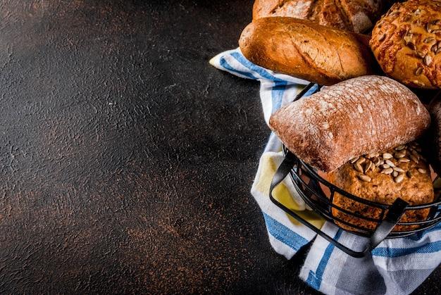 Variedade de pão caseiro fresco, em uma cesta de metal, copyspace enferrujado escuro