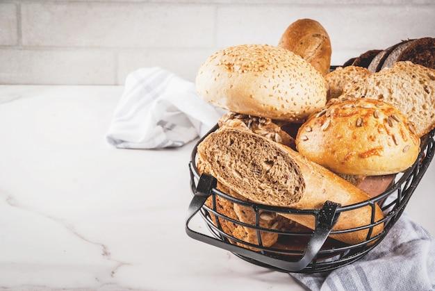 Variedade de pão caseiro fresco, em uma cesta de metal, mármore branco copyspace