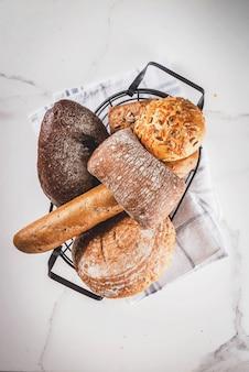 Variedade de pão caseiro fresco, em uma cesta de metal, vista superior de mármore branco copyspace