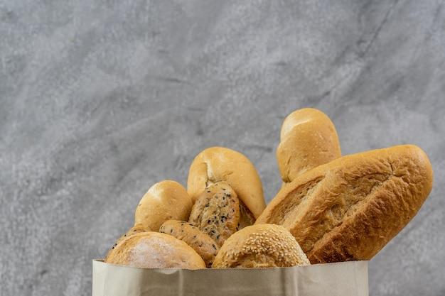 Variedade de pão em saco de papel descartável. comida e bebida de padaria e conceito de mercearia para entrega.