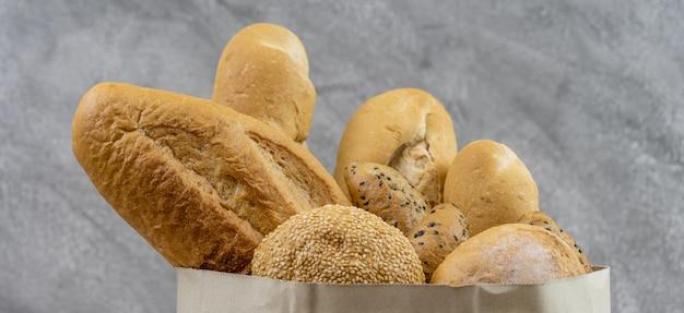 Variedade de pão em saco de papel descartável. panorâmico
