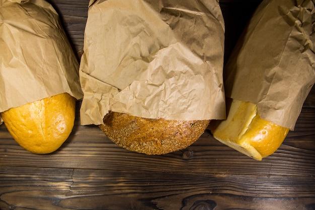 Variedade de pão embalado em papel na mesa de madeira. vista superior, copie o espaço