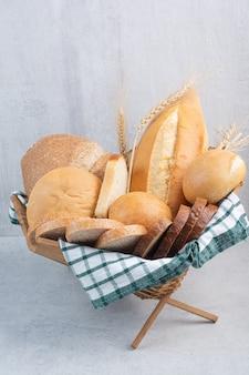 Variedade de pão na cesta na superfície de mármore