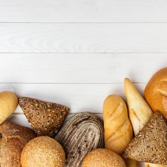Variedade de pão no fundo da mesa de madeira branca. vista superior com espaço de cópia