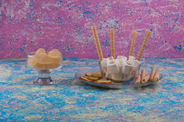 Variedade de pastéis em copo de vidro e bandeja em fundo rosa