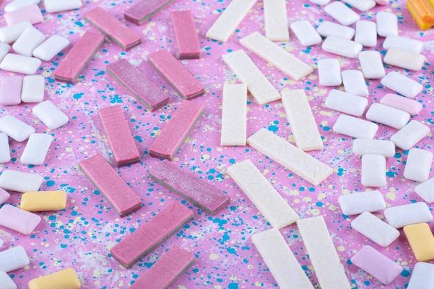 Variedade de pastilhas de goma de mascar espalhadas sobre uma superfície colorida