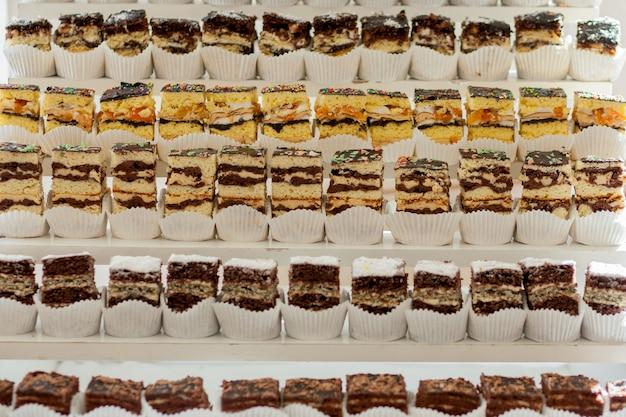 Variedade de pedaços de bolo na mesa desarrumado, copyspace. várias fatias de deliciosas sobremesas, menu de restaurante, vista superior