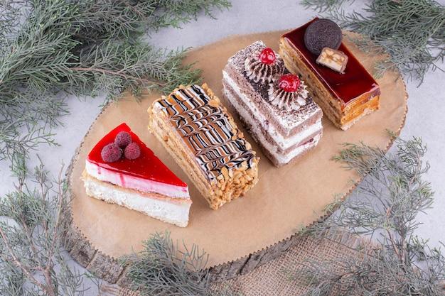 Variedade de pedaços de bolos na peça de madeira. foto de alta qualidade