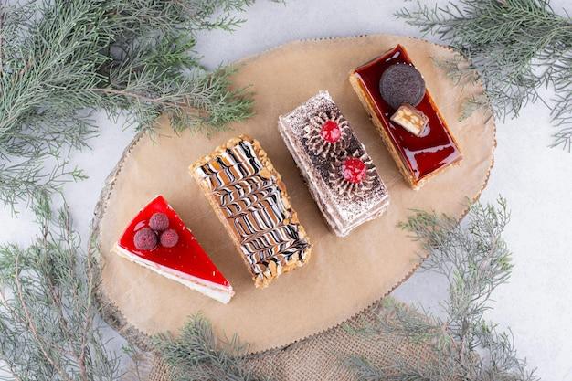 Variedade de pedaços de bolos na peça de madeira.