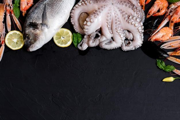 Variedade de peixes e frutos do mar saudáveis em fundo preto. vista do topo. frutos do mar em fundo preto rústico.