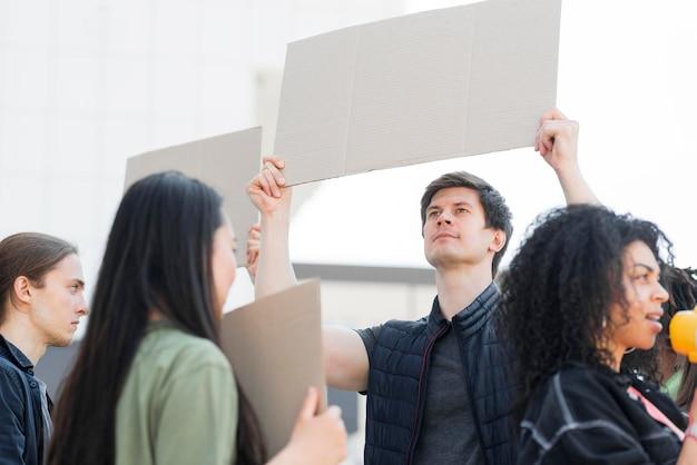 Variedade de pessoas que protestam nas ruas segurando cartões