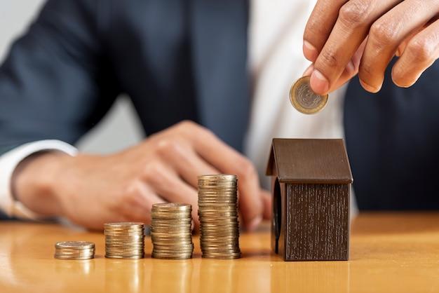 Variedade de pilhas de moedas e caixa de dinheiro da casa