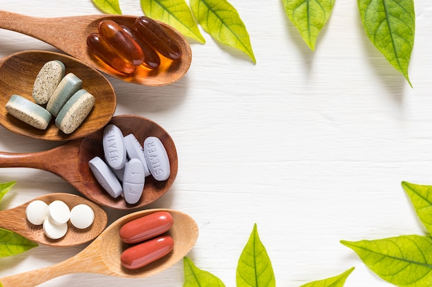 Variedade de pílulas de vitamina em colher de madeira no fundo branco com folha verde, plana le