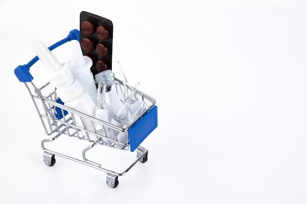 Variedade de pílulas em embalagens blister em um mini carrinho de compras em um fundo branco