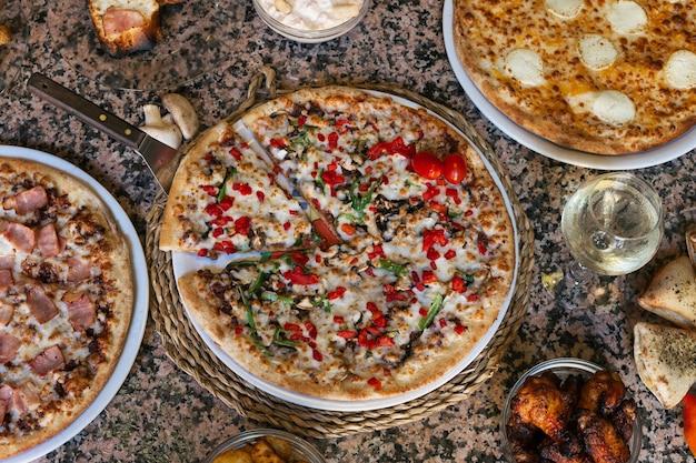 Variedade de pizzas e tapas na mesa de granito