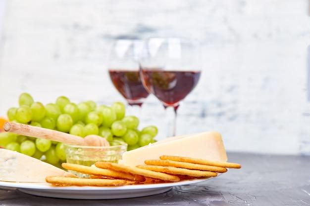 Variedade de prato de queijo e vinho em copos