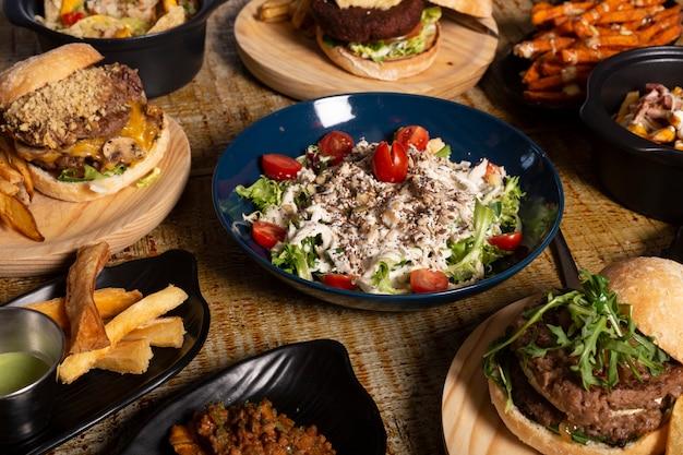 Variedade de pratos de estilo mexicano. menu de restaurante, salada, mandioca frita e hambúrgueres na mesa de madeira.