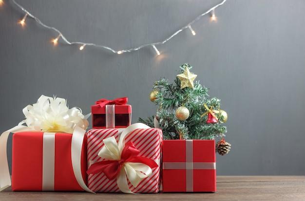 Variedade de presente vermelho fundo de conceito de caixa de natal feliz. objetos deferentes em madeira rústica na mesa de escritório de estúdio e espaço de cópia. decoração festiva também feliz ano novo ou outra estação.