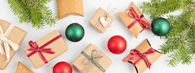 Variedade de presentes de natal embrulhados em papel e bugigangas vermelhas e verdes com galhos de pinheiro, planta plana, vista de cima