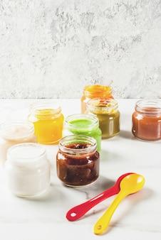 Variedade de purê de frutas e vegetais de bebê caseiro, copyspace de mármore branco