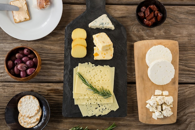 Variedade de queijo, azeitonas, biscoitos e ervas de alecrim na mesa de madeira