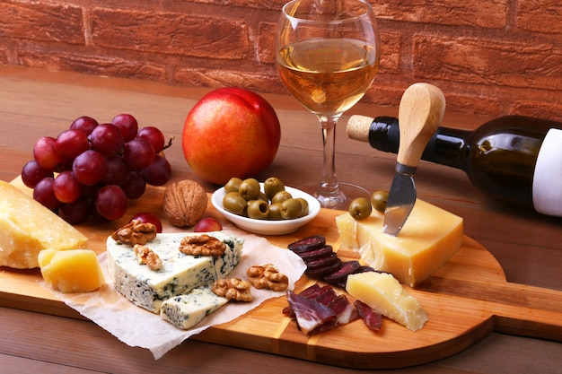 Variedade de queijo com frutas, uvas, nozes e faca de queijo em uma travessa de madeira.