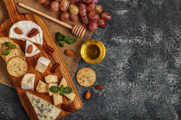 Variedade de queijo com mel, nozes e uva em uma tábua de cortar, vista superior