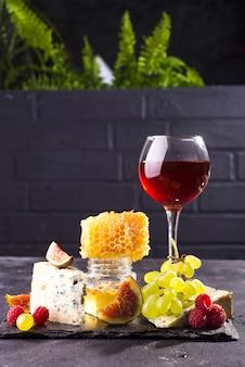 Variedade de queijo, frutas e uvas com vinho tinto em copos na pedra.