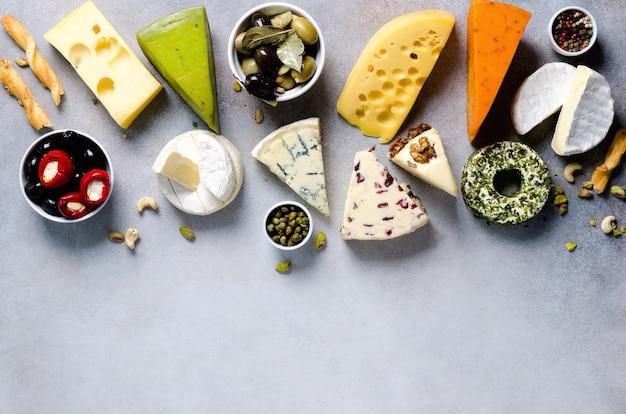 Variedade de queijos duros, semi-moles e macios com azeitonas, varas de pão grissini, alcaparras, uva, no backgound concreto cinzento. vista de cima, copie o espaço, lay plana. prato de aperitivo de seleção de queijo.