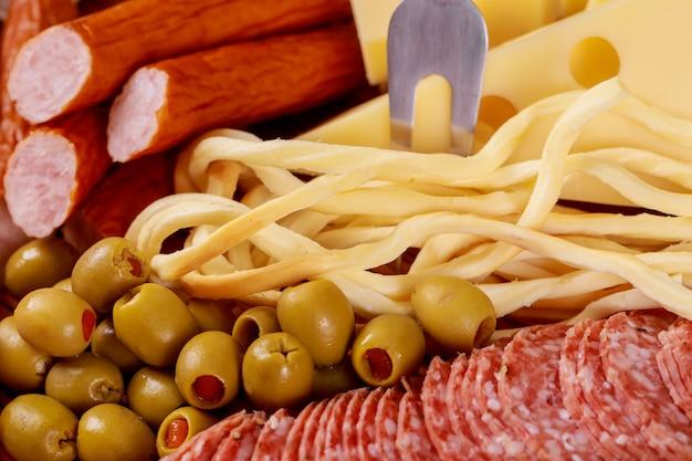 Variedade de queijos e azeitonas e salsichas na mesa